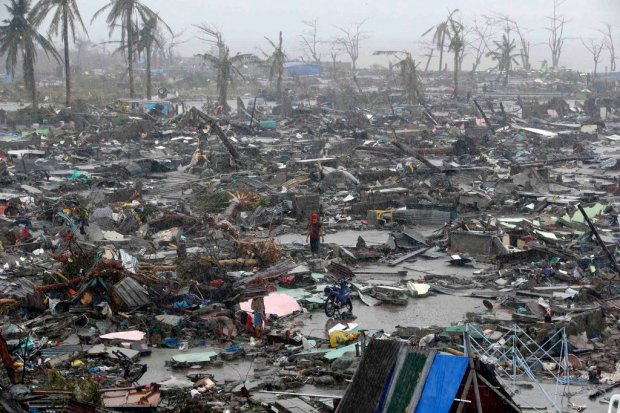 People stood among the ruins of houses destroyed by Typhoon Haiyan in Tacloban, Philippines, a city of about 220,000. (C) NY Times